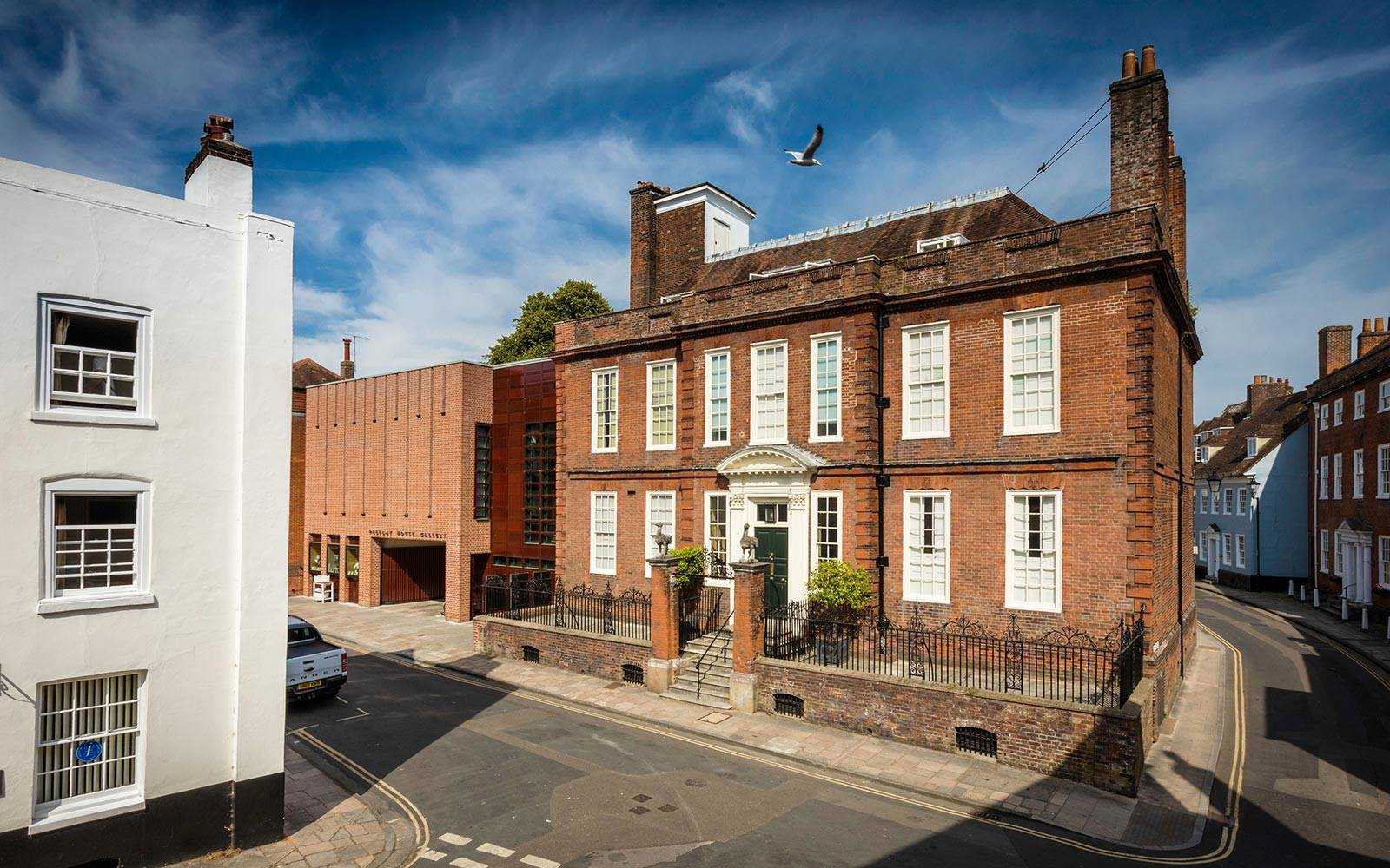 Image of a red brick Georgian townhouse joined to a contemporary extension on a sunny day.