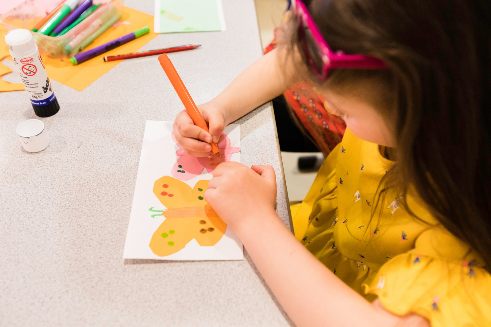 A young girl decorstes a piece of paper with a yellow butterfly design