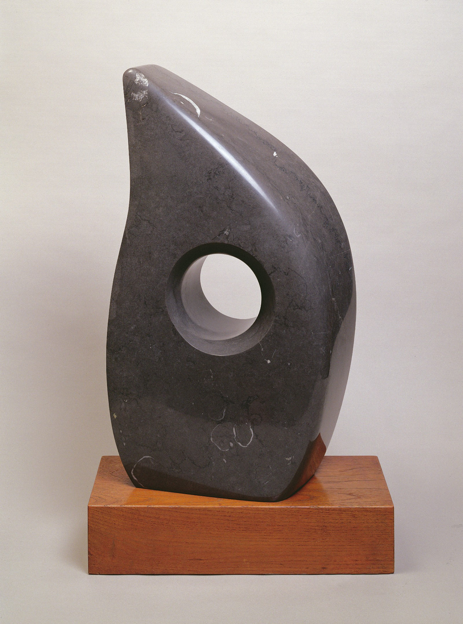 A black marble sculpture in the spae of a tear drop with a hole in its centre.