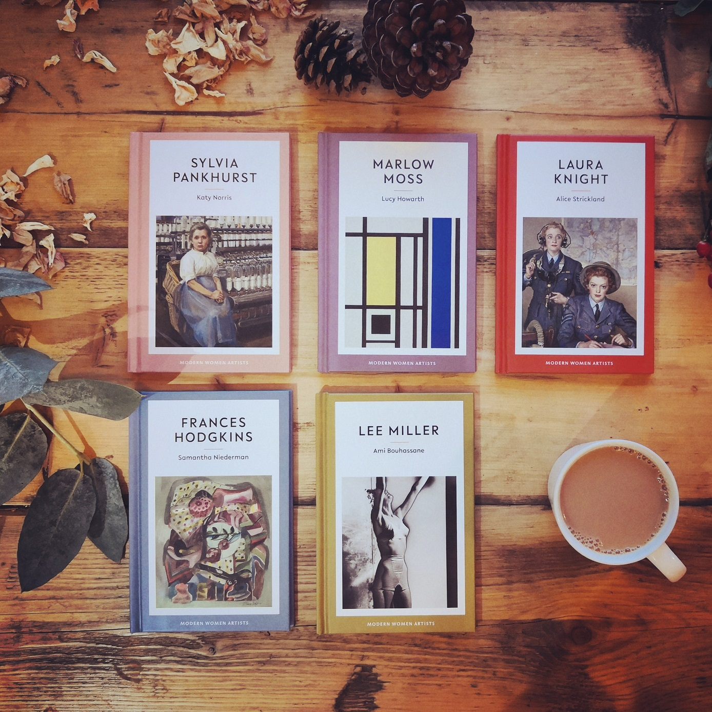 Photograph of the range of five Eiderdown Press books on a wooden floor next to a cup of tea.