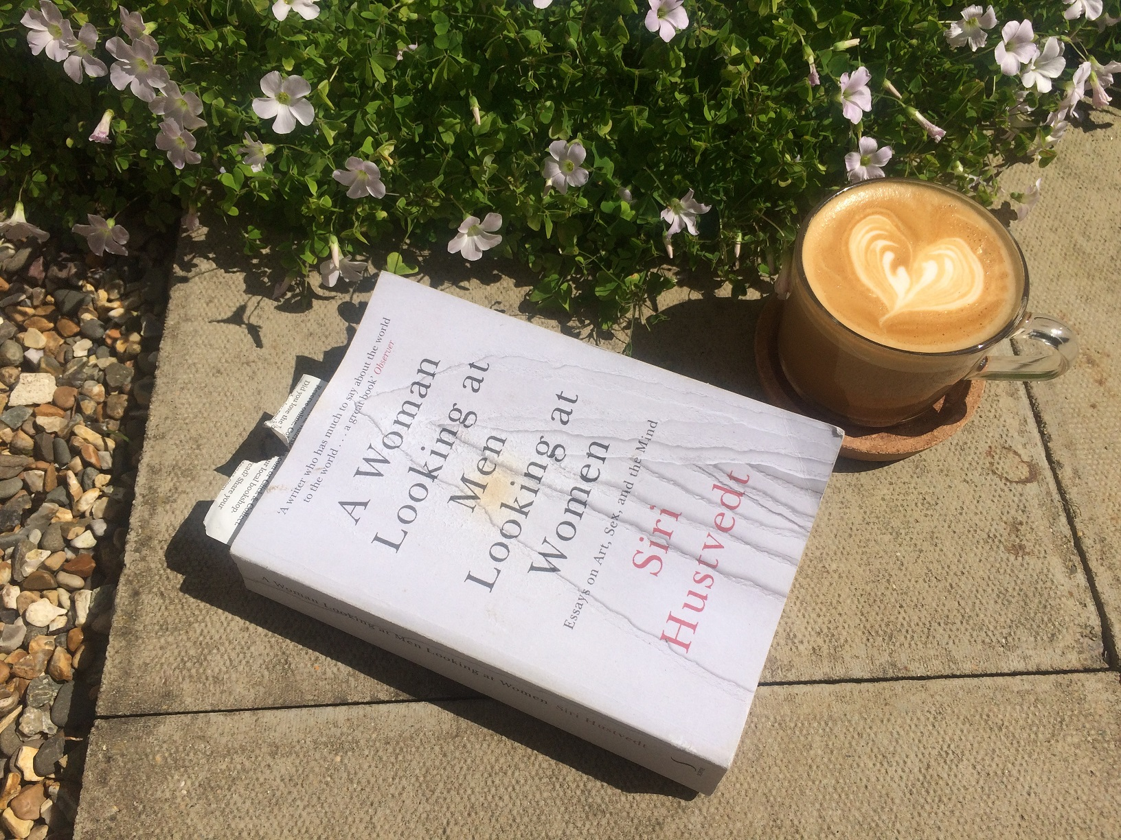 A photograph of the book 'Women LOoking at Men' by author Siri Hustvedt on a garden paving stone with a coffee and some plants.