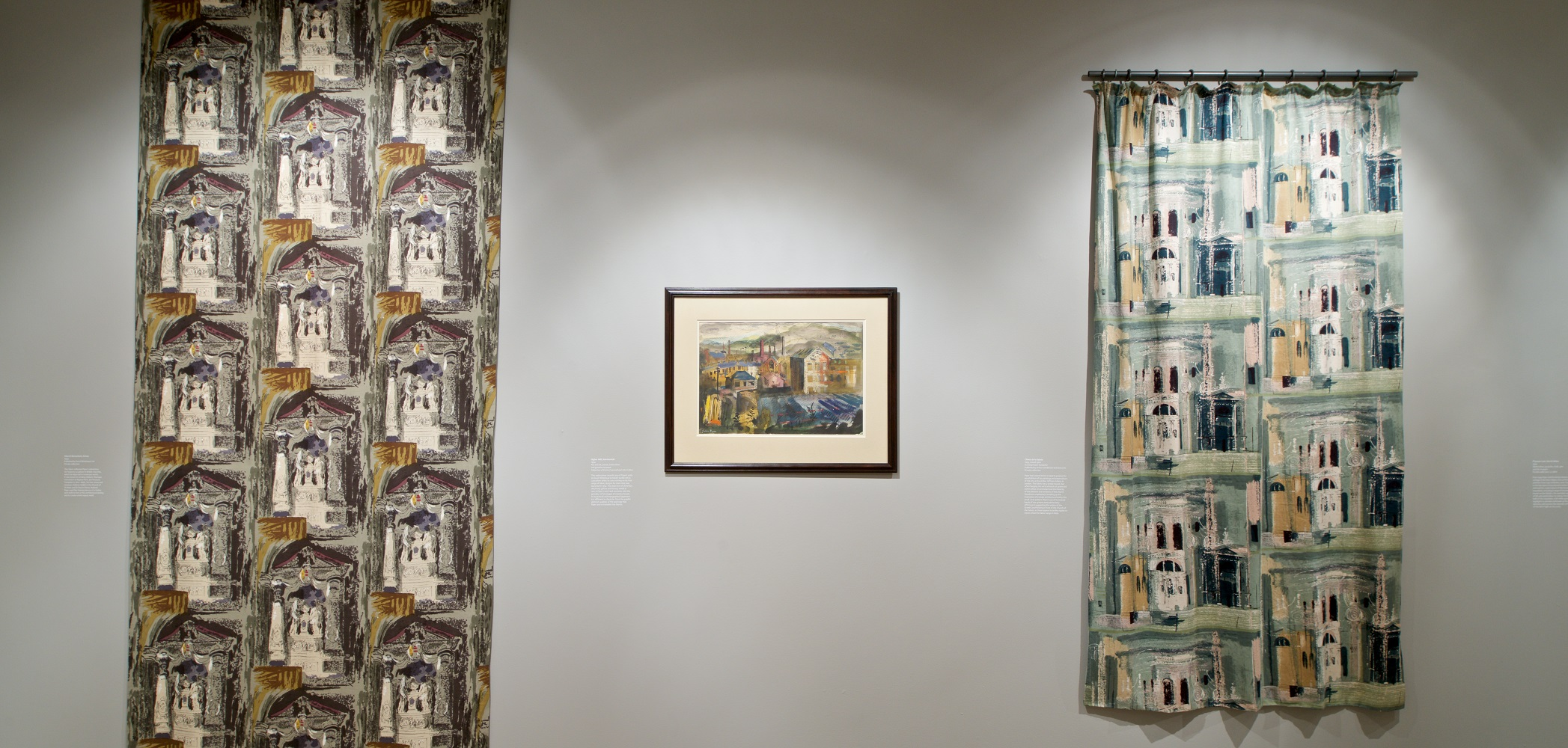 View of interior of gallery showing two lengths of cloth with two different abstract designs. Between them is a painting showing a mid-century urban landscape.