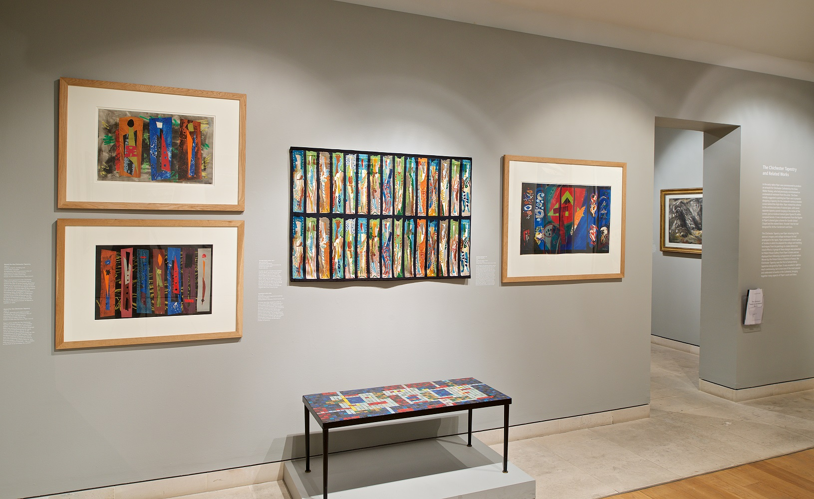 View of gallery showing four abstract wprks of art on the wall with a mosaic table below