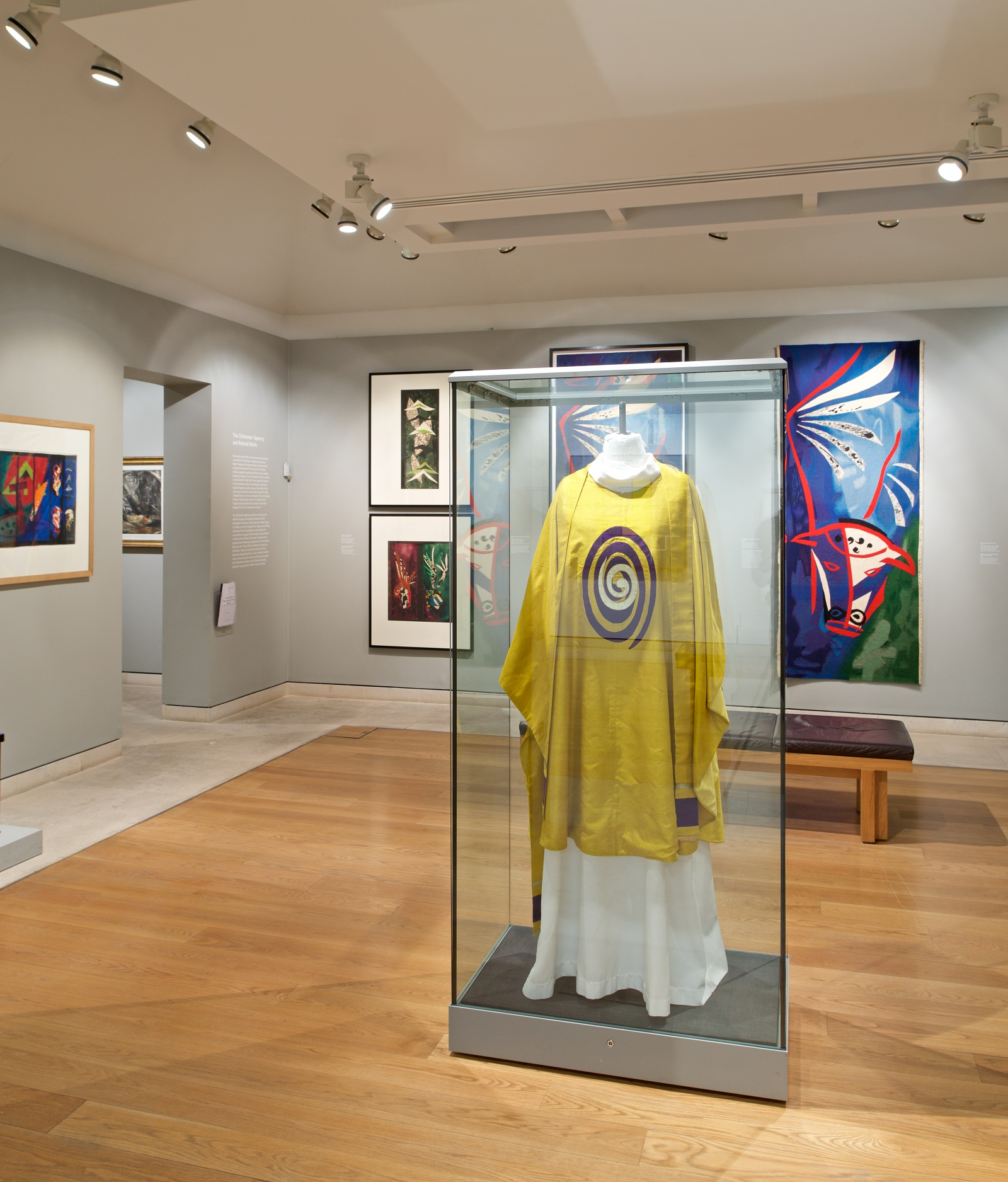 View of gallery showing abstract works of art on the wall. In the centre is a glass case containing a mannequin wearing a yellow vestement with abstract oval design on its chest