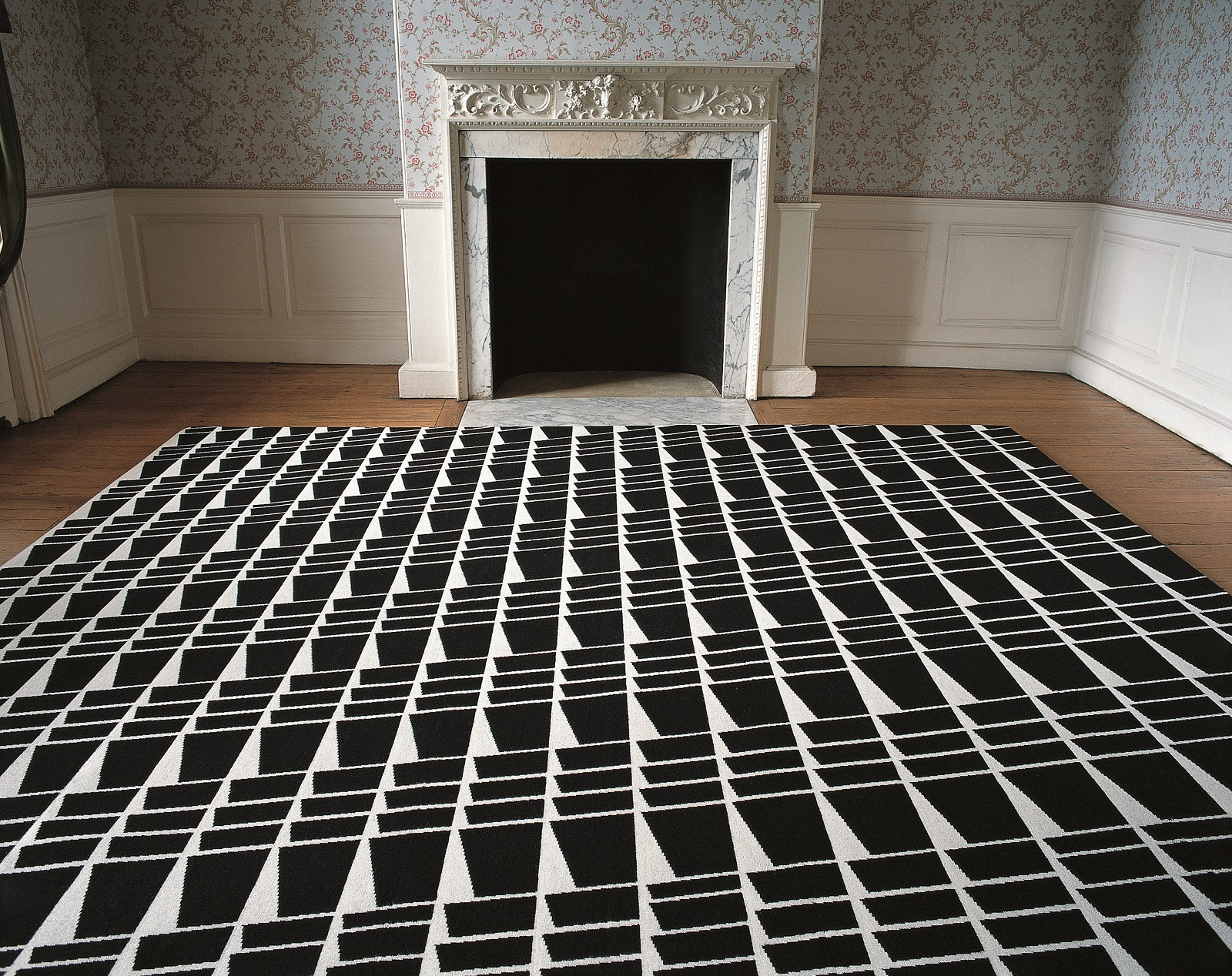 A black and white rug in a geometric pattern laid out in front of a period fireplace in a room with floral wallpaper