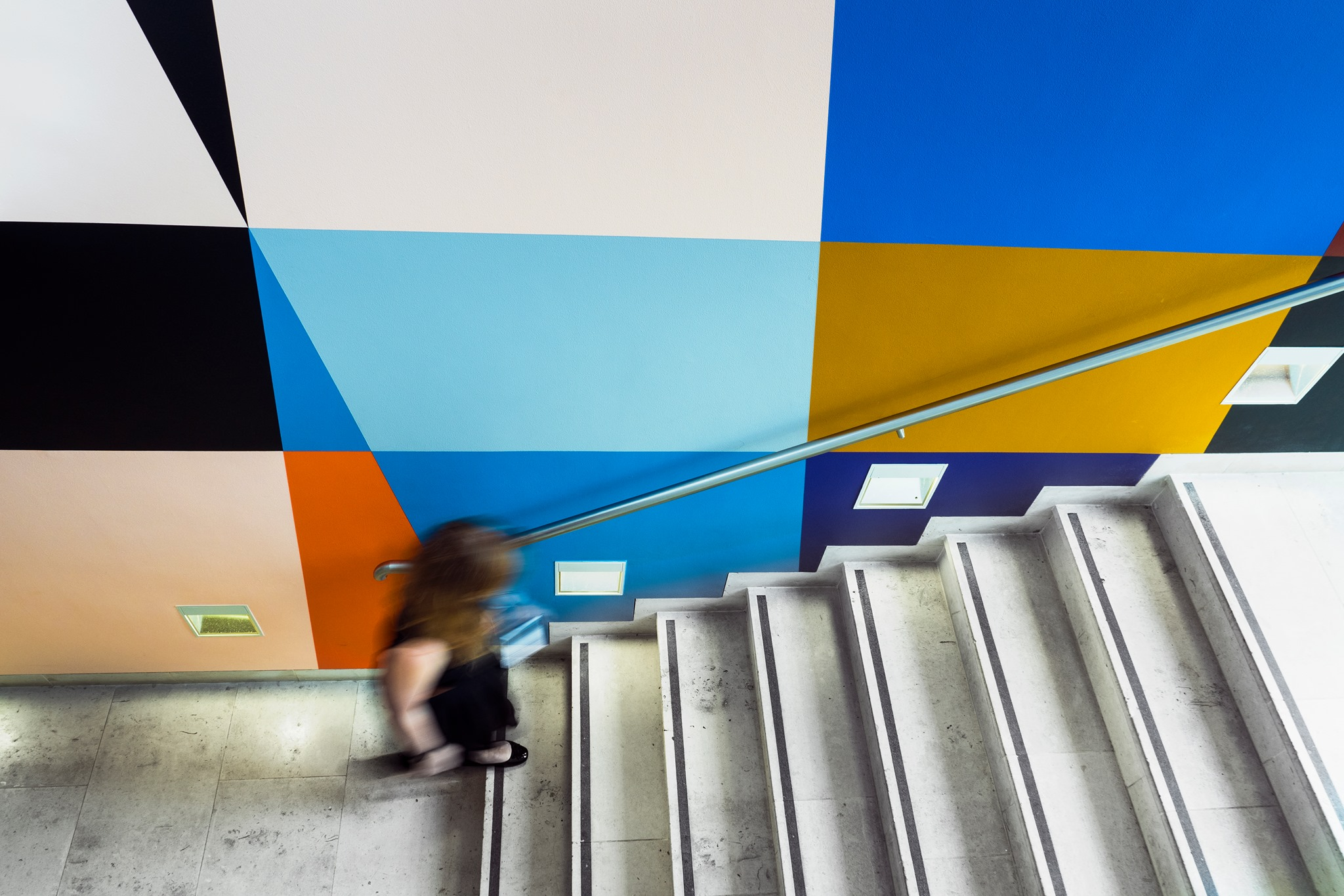 View looking down a stairwell decorated with a colourful geometric mural as a woman dressed in black climbs the stairs.