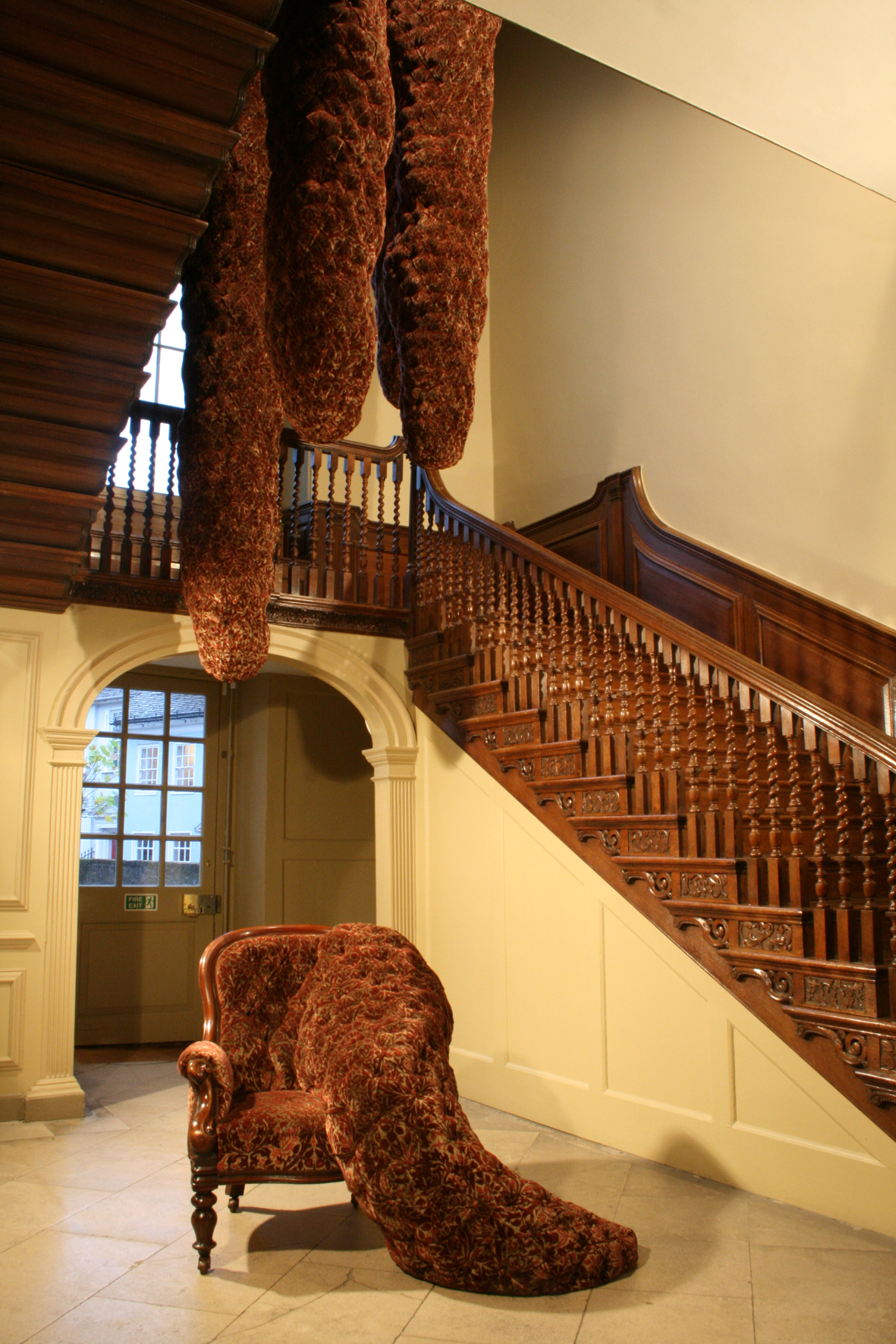 A period staircase with a red upholstered armchair with amorphous bulging out of one side at the foot of the staircase. More long upholstered forms hang down the centre of the stairwell.