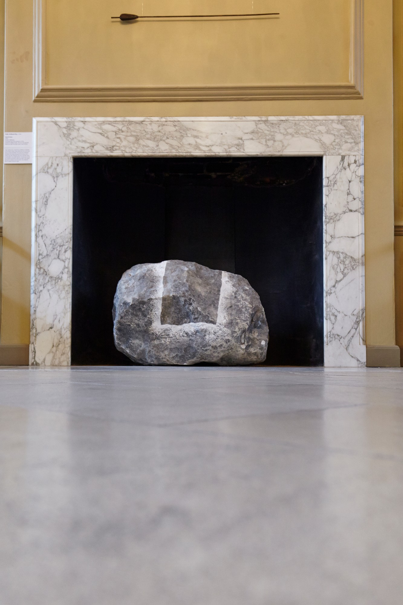 A large chalk stone incised with a square outline sitting in a period fireplace.