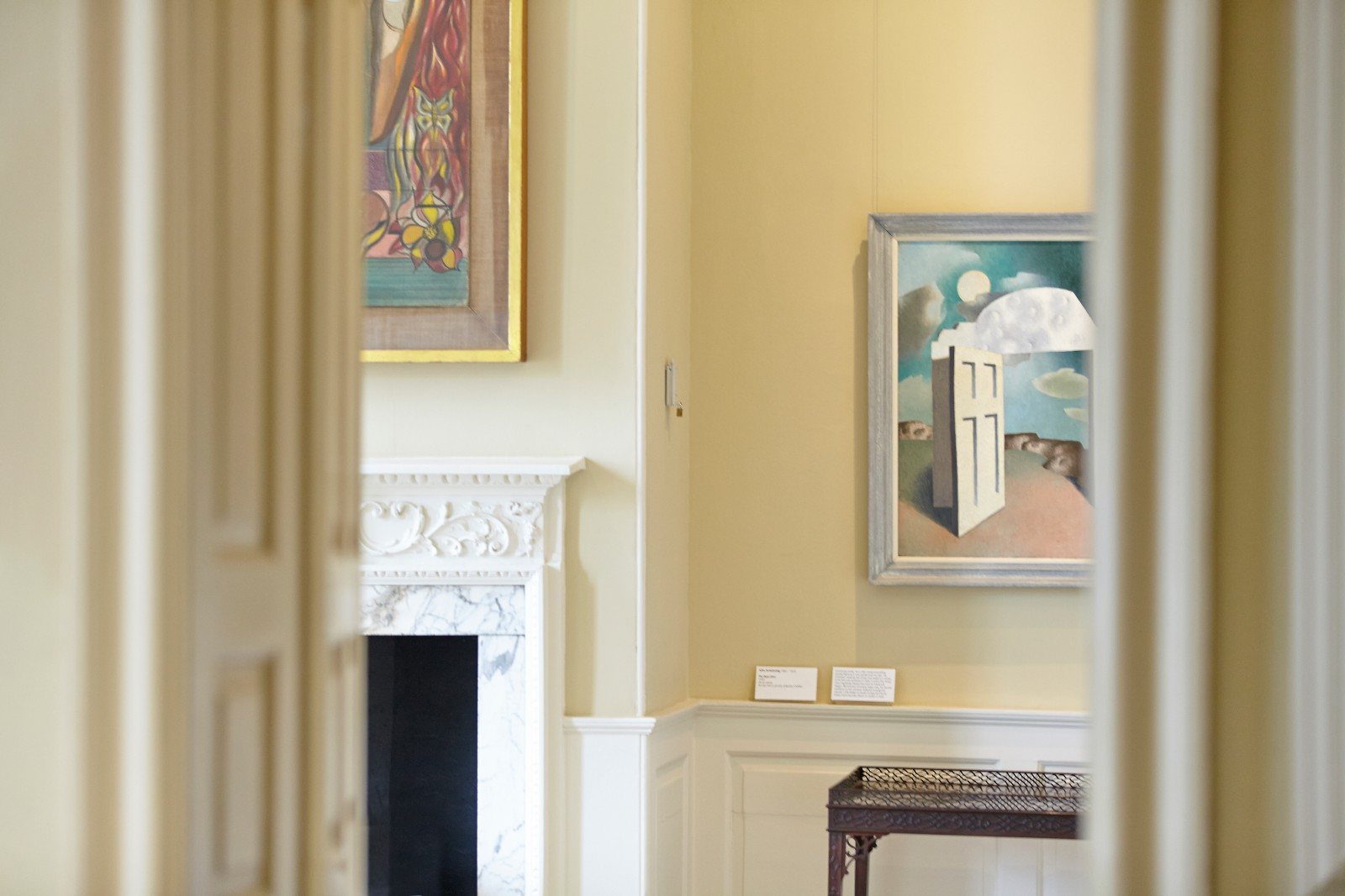 An interior view of a period house looking through a doorway into a room hung with modern art.