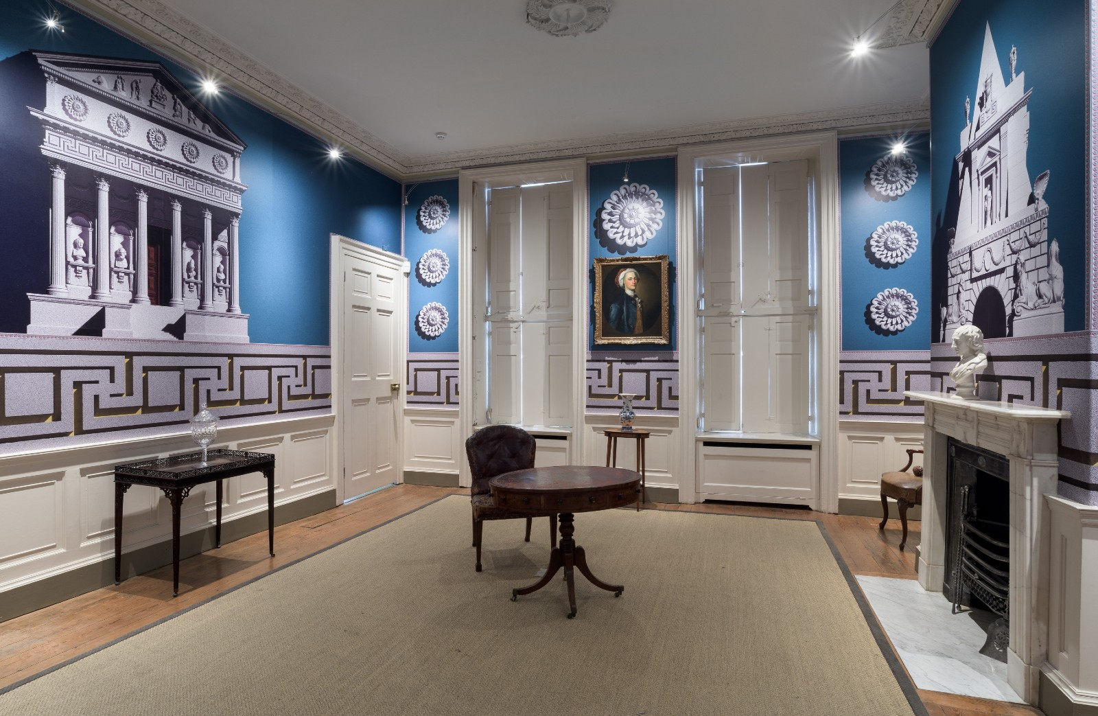 The interior of a period house with wallpaper decorated with outsized classical buildings and architectural features against an electric blue background.
