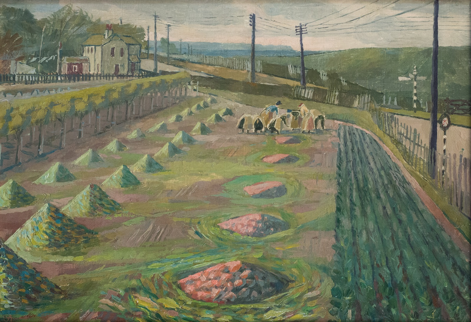 A field with furrowed rows and piles of crops with a group of women working in the distance