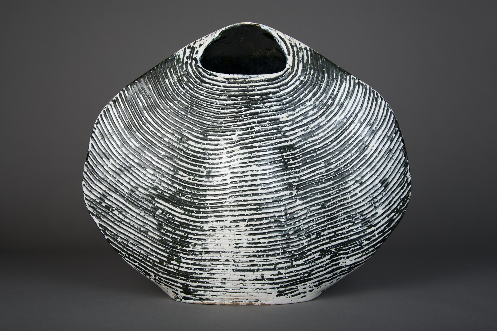 Large cockle shell shape vase with small opening at the top modelled in creamy grey. The ridges in the clap look black.