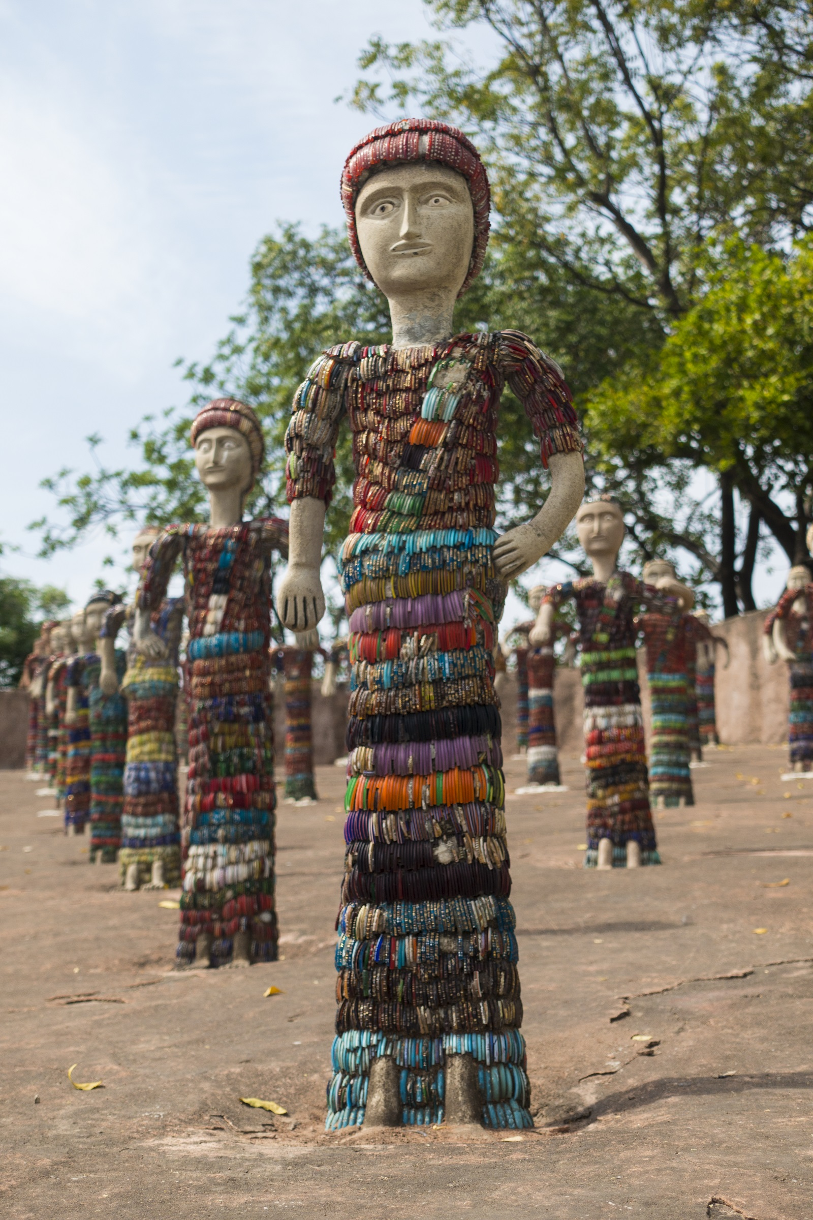 Row of brightly decorated sculptures of people made from discarded pottery fragments