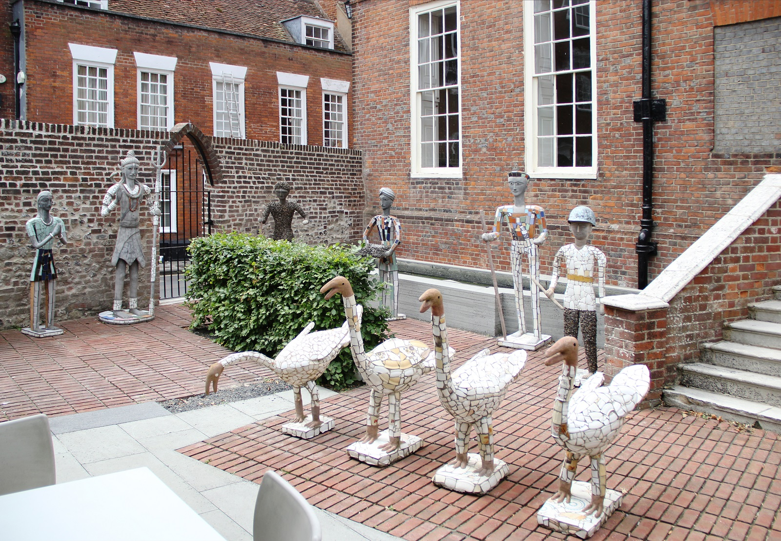 A set of four swan sculptures stand in a row in front a row os sculptures of human figures. All the sculptures are made from concrete and discarded pottery fragments