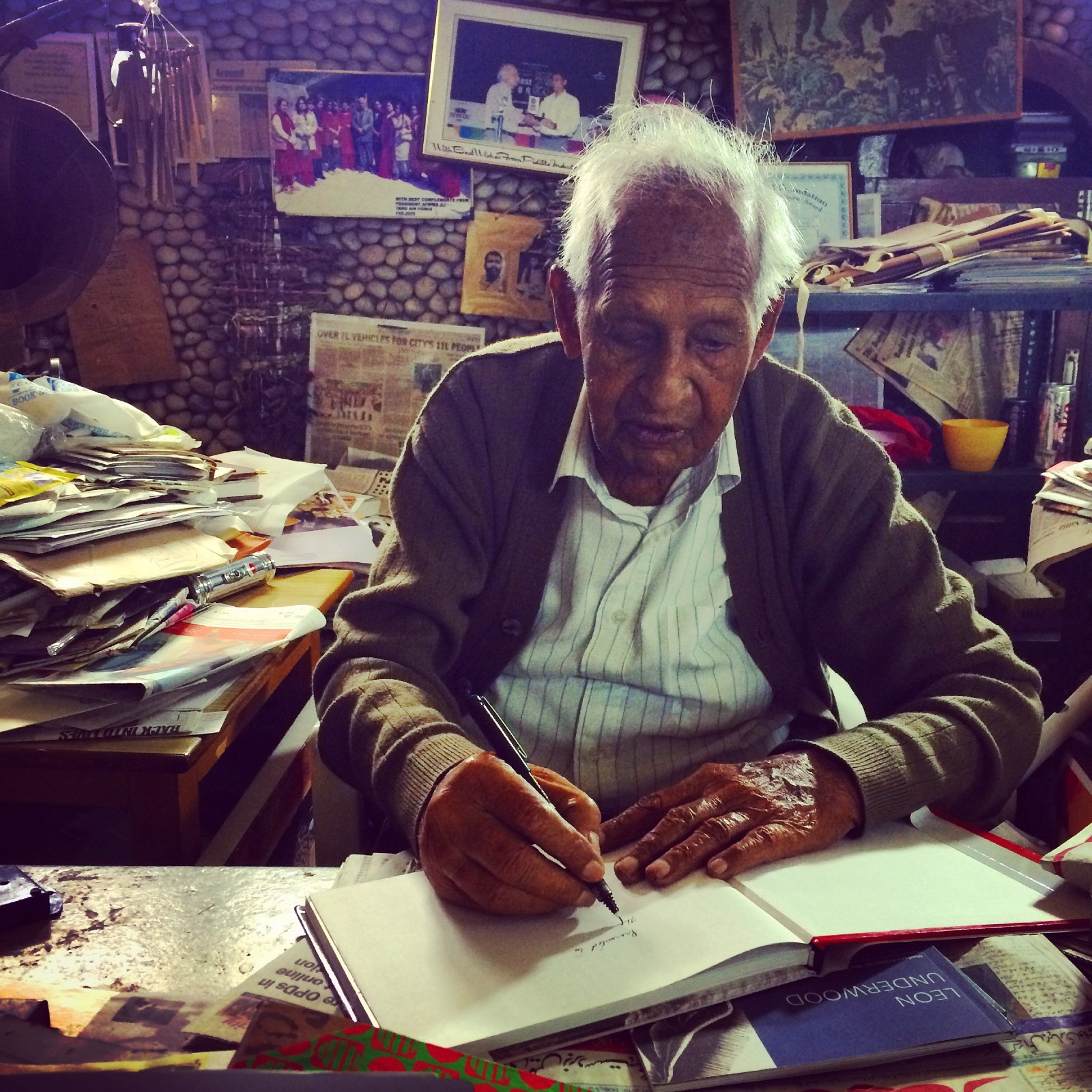 An elderly Indian man draws ina sketchbook surrounded by piles of paper, photographs and other ephemera