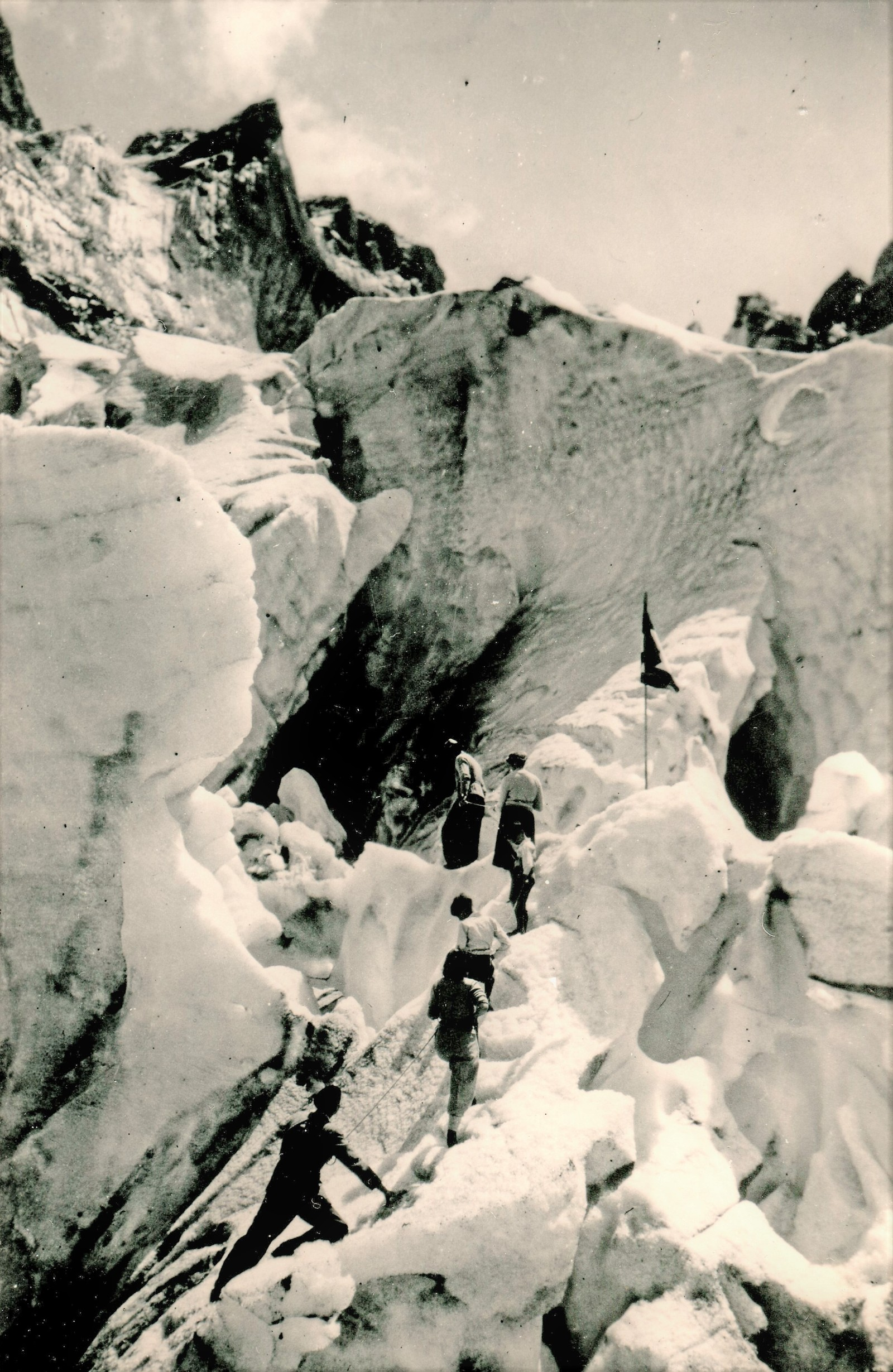 A black and white photograph showing a group of six people walking up the steep sides of a glacier, tethered together by rope.