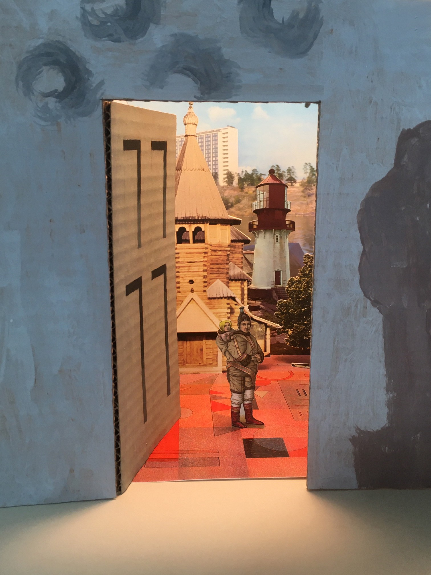 A piece of cardboard decorated to look like a wall with a door opens onto a surreal collage landscape showing a woman carrying a child with a variety of buildings in the background including a tower block and a lighthouse