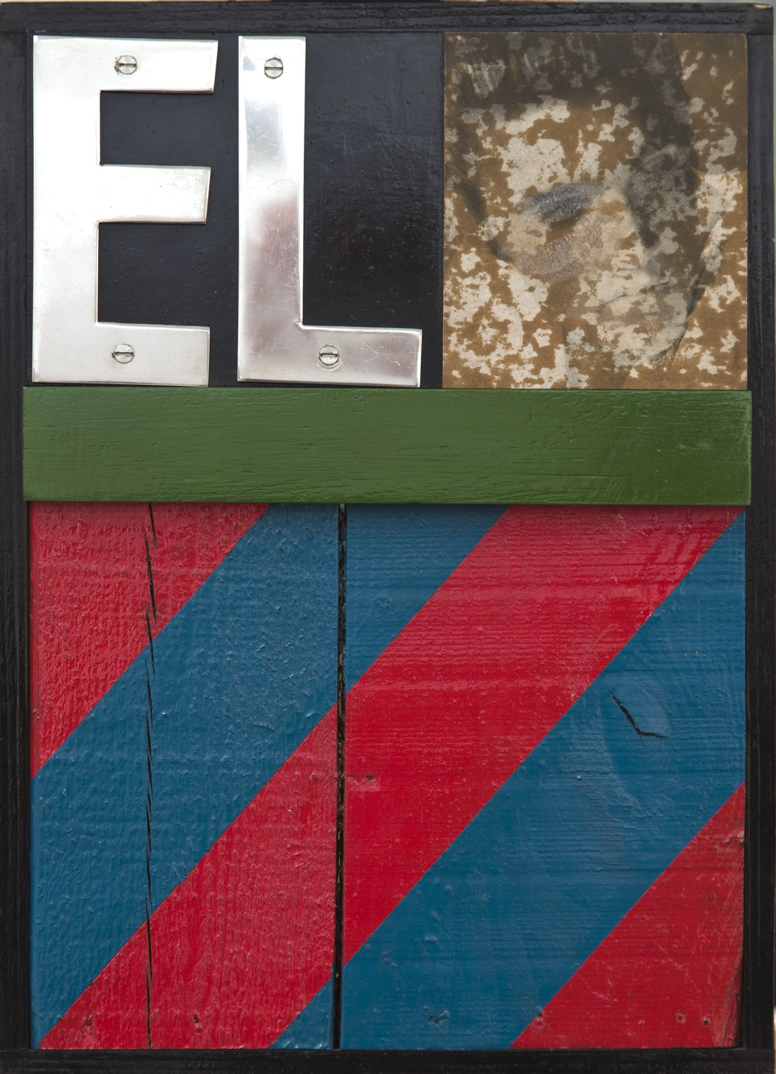 Wooden boards painted with red and blue diagonal stripes oin the lower half. In the top left corner are the letters E and L and in the right corner there is a distressed photograph of Elvis Preslet smeared with lipstick