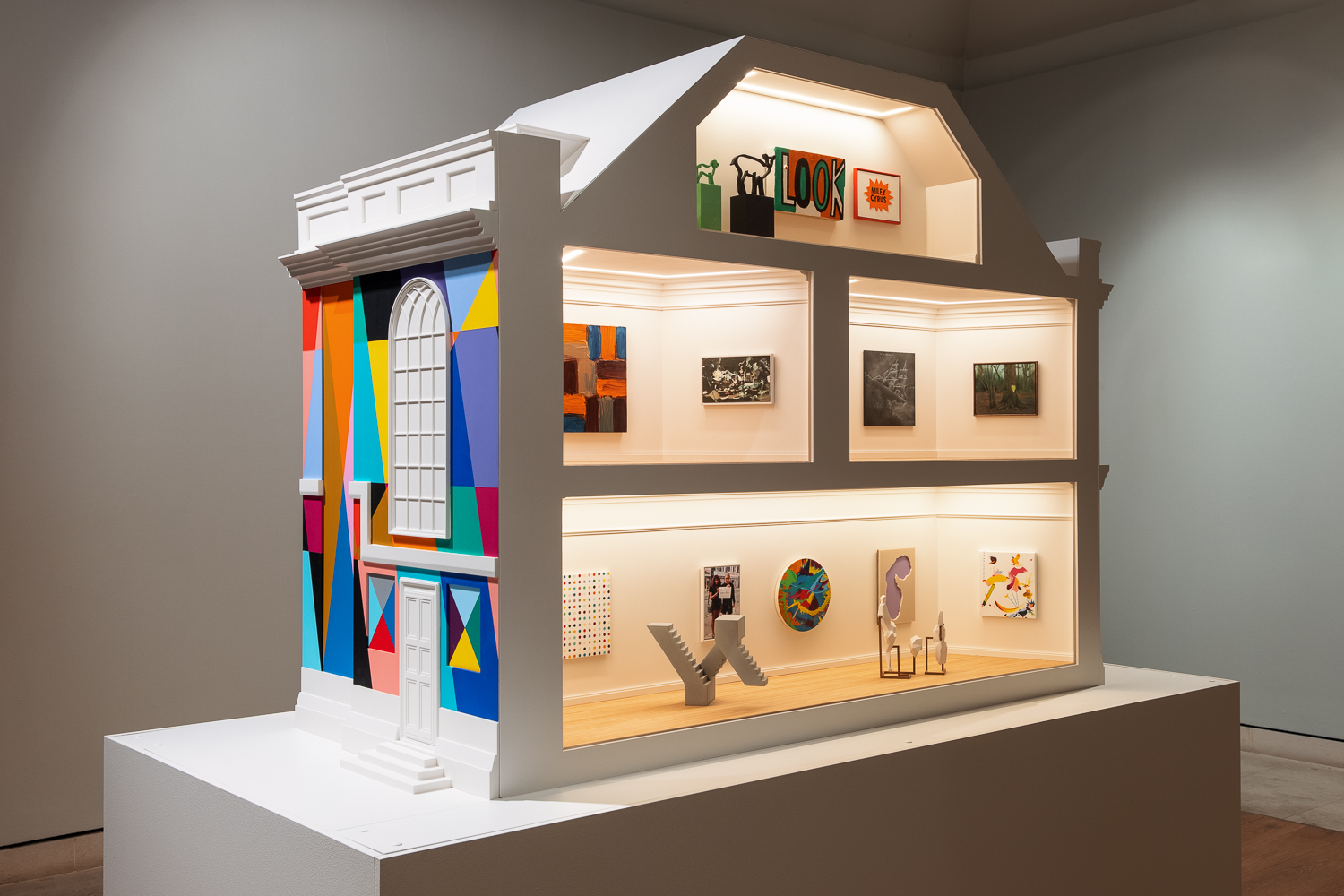 A large dollhouse sized art gallery, designed to imitate the exterior of an 18th century townhouse. The left hand side is painted with a brightly coloured geometric mural. The right side shows a cross section of four rooms (one in the attic, two on the first floor, and one on the ground floor), each filled with works of modern art.