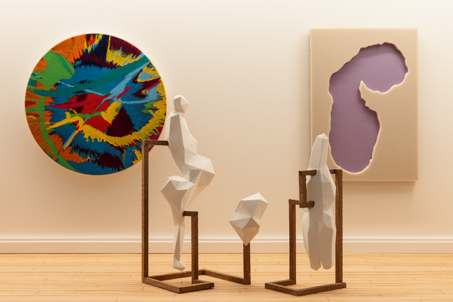 Three works of art in a gallery with white walls and wooden flooring. On the back wall to the left is a painting on a round canvas decorated with splotches of paint applied when the canvas was spinning to create an explosive effect. On the right is work showing a lilac land mass sunk in relief in a white canvas. In front of both is an abstract sculpture of white abstract blocks balanced on wooden stands.