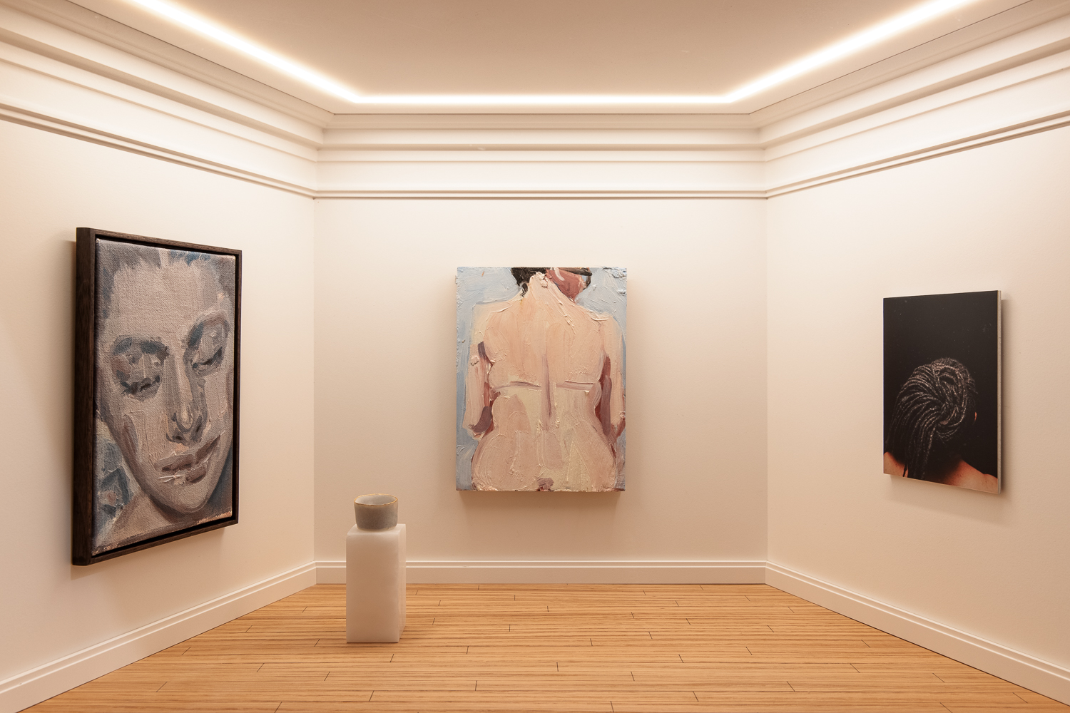 Four works of art in a gallery with white walls and wooden flooring. On the left wall is a close up portrait of a woman's face painted in grey and blue tones. On the back wall in the centre is a painting of a woman's bare back. On the right wall is a photograph of the back of a woman's head, showing her intricate braided hair. On a plinth towards the left side is a ceramic pot, edged with gold.