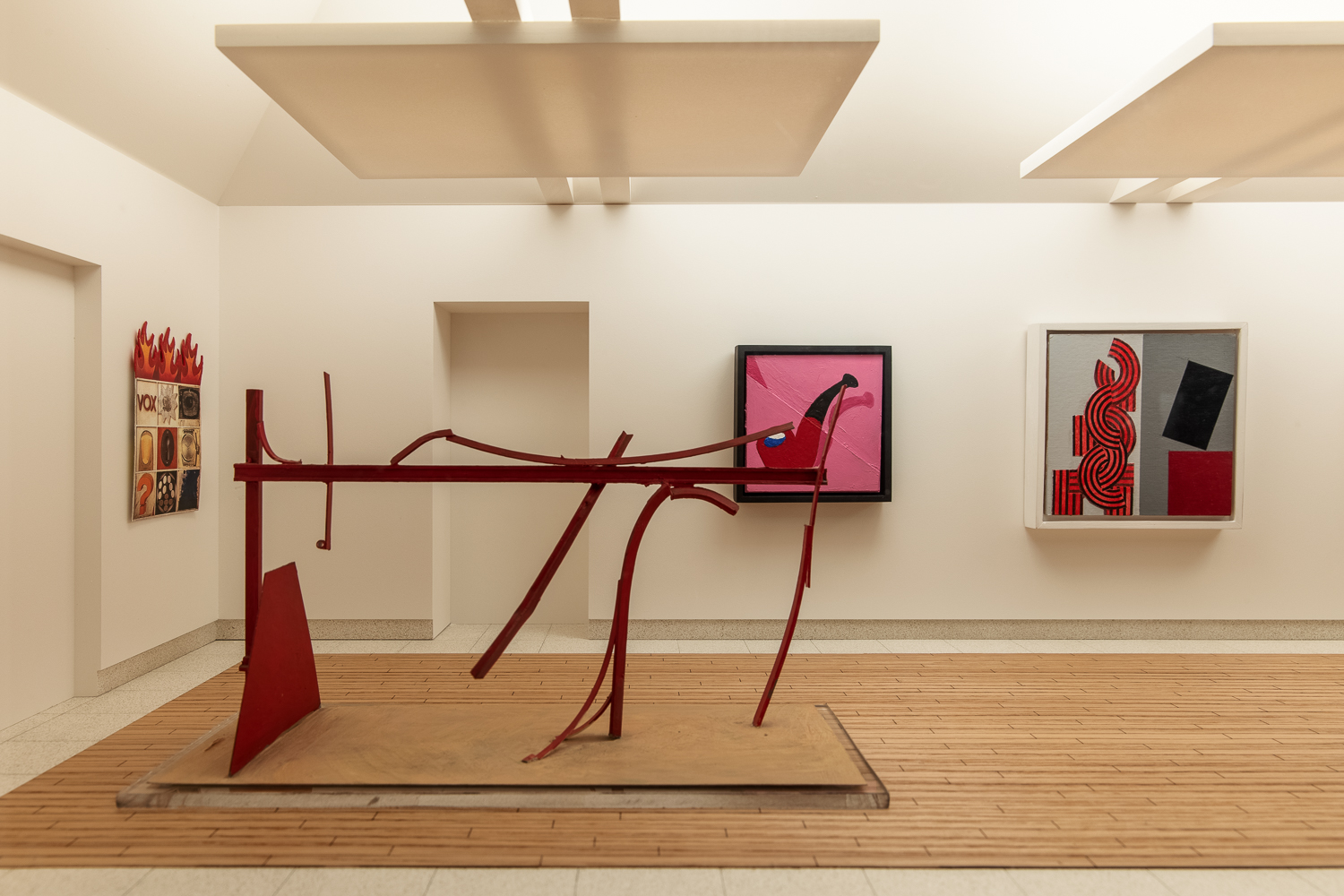A model art gallery room with white walls, a dropped ceiling and wooden and stone look flooring. On the left hand wall is a painting with nine boxes containing different words, images and symbols and with thhree flames coming out the top of it. In the centre is a painting of a red pipe against a pink background. To the right of that is an abstract painting with a two tone grey background and blocks of red and black. In the foreground and to the left is a red metal abstract sculpture.