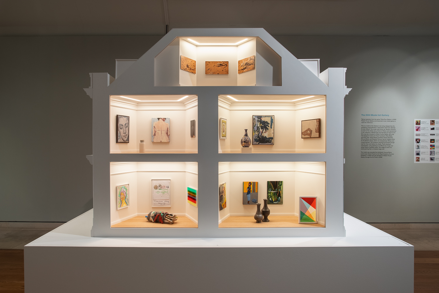 A large dollhouse sized art gallery, designed to imitate the exterior of an 18th century townhouse. The front shows a cross section of fiverooms (one in the attic, two on the first floor, and two on the ground floor), each filled with works of modern art.