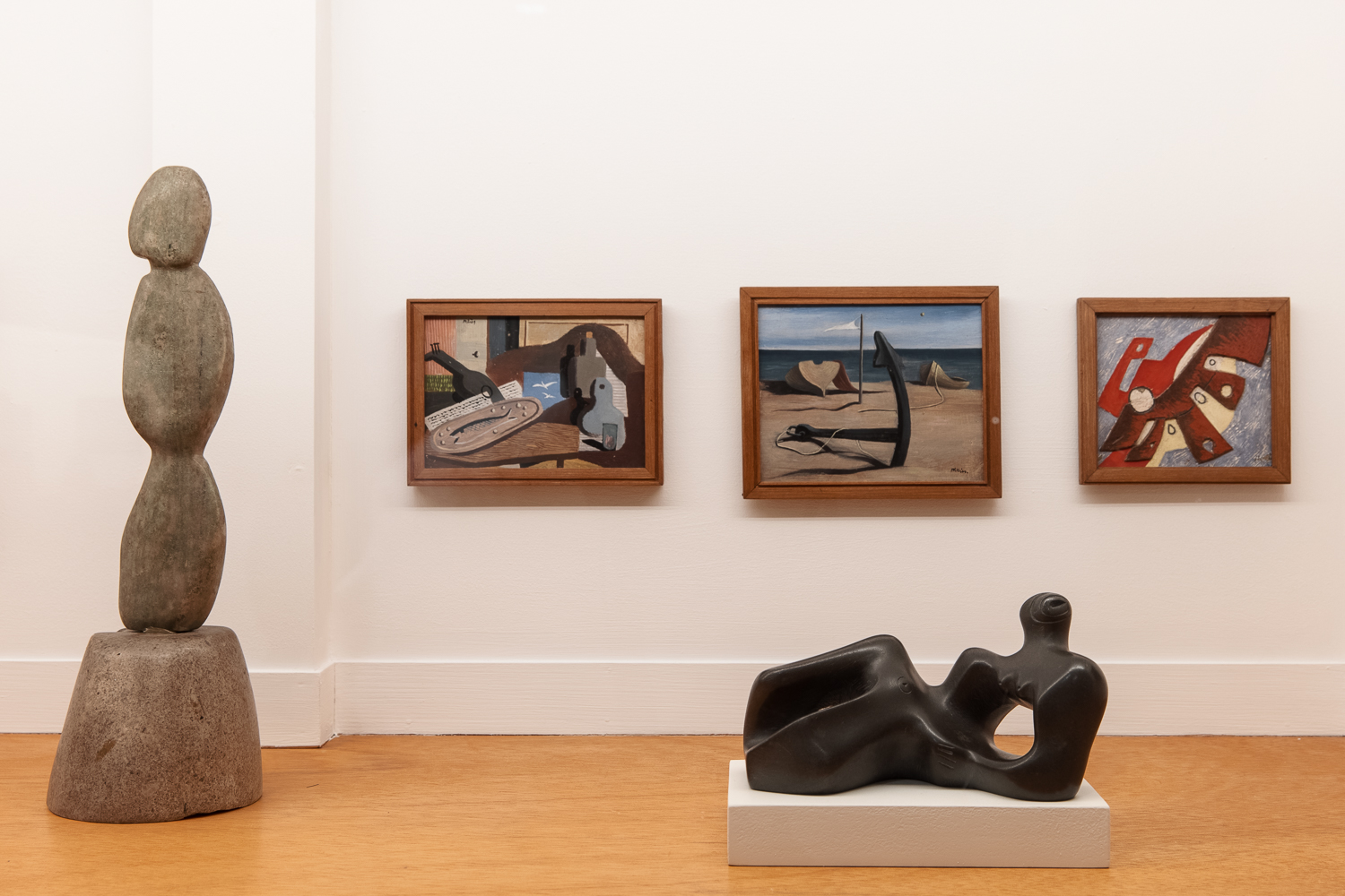 Five works of art in a gallery with white walls and wooden flooring. On the left side is a sculpture of three oval forms stacked on top of each other. On the back wall are three paintings of abstracted still lifes and still lifes. In the foreground is a Henry Moore sculpture of an abstracted reclining human figure.