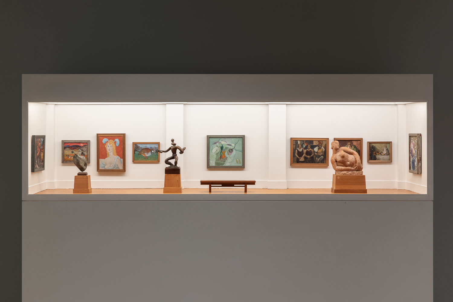 A model art gallery with white walls and a wooden flooring, filled with miniature paintings, sculptures and a bench.