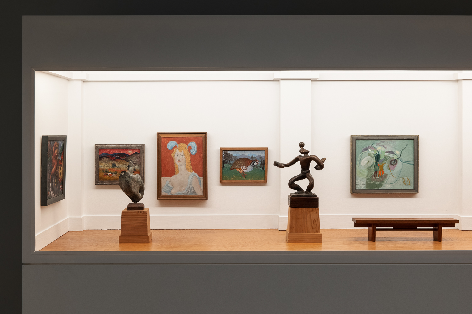 Seven works of art in a gallery with white walls and wooden flooring. One painting is on the left hand wall and four (depicting a landscape, a portrait of a woman, a grouse and an abstract painting of flowers) are on the back wall. In the foreground are two sculptures; the one on the left is an abstracted sculpture of a seabird rising from water and the other is a human figure, juggling. To the right of that sculpture is a wooden bench.